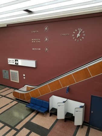The escalator in the international terminal area with four clocks on the wall behind it giving the time of day in Gander, London, New York, and Moscow.