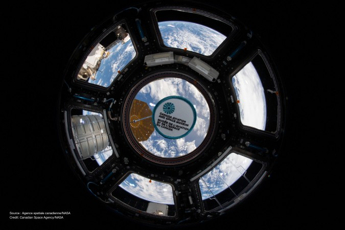 "A small badge with the words ""Canada Aviation and Space Museum"" is framed against the window of the International Space Station, with the Earth in the background."