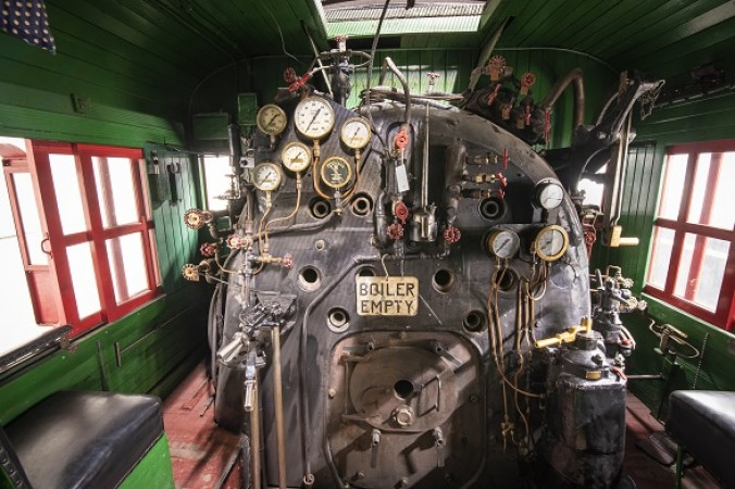 View of a locomotive's boiler room, with a series of gauges and knobs.