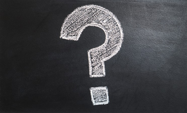 A large white question mark drawn on a black chalkboard.