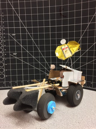 A rover prototype, made of various materials, sits on a desk.