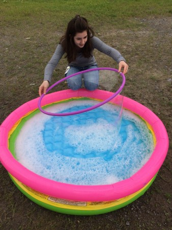 Intern Charlotte Clemens, attempting to make a giant bubble by pulling a hula hoop out of a kiddie pool.