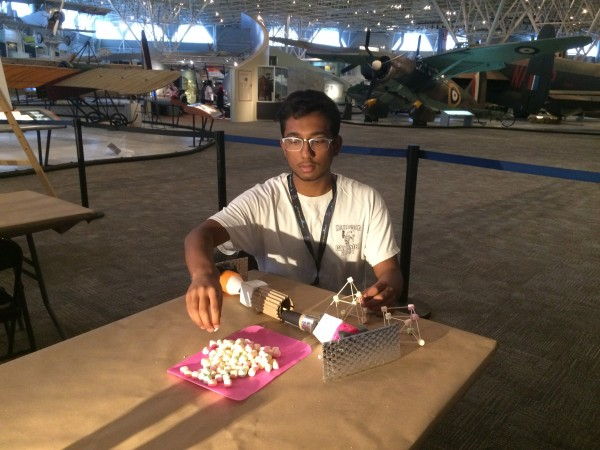 The author sits at a table and assembles a contraption using small marshmallows and other materials.