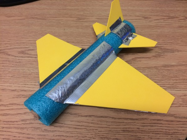 A pool noodle airplane with wings and a tail made out of yellow foam and pieces of cardboard.
