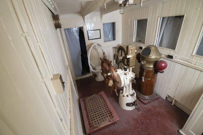 An aerial view of the steering wheel and other pieces of equipment, inside the wood-panelled walls of the pilot house.