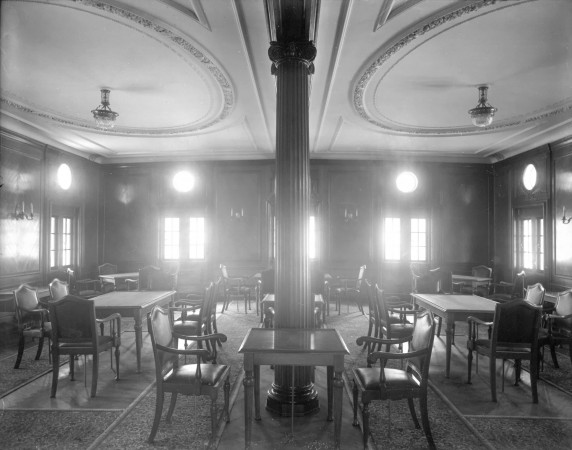 A black-and-white image of a formal dining saloon, filled with elegant tables and chairs.