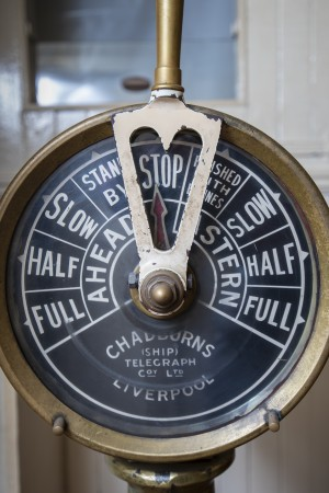 A close-up view of an old brass dial, which served as the engine room's telegraph.