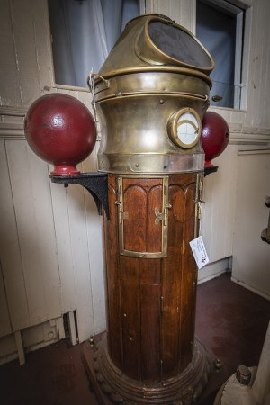 A tall wooden-and-brass column called the binnacle, which houses the ship's magnetic compass.