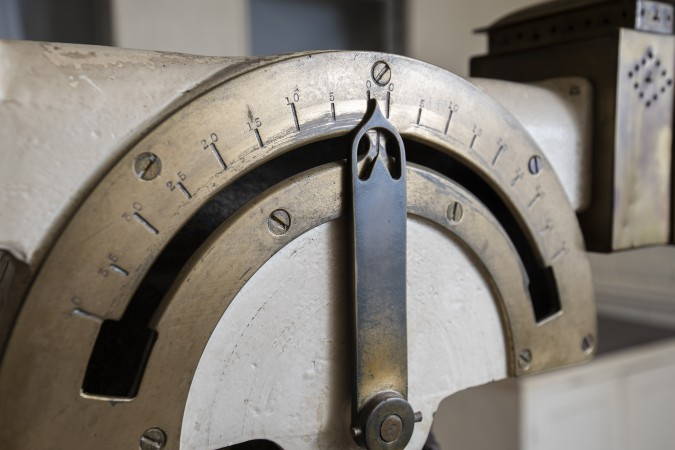 A close-up view of an old brass dial, which served as the rudder position indicator.