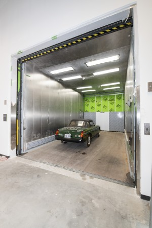 A green sports car looks tiny as it sits inside the oversized freight elevator.
