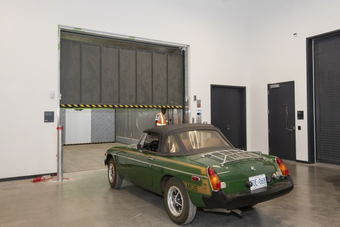 A worker opens the large elevator door, as a green sports car sits in front.