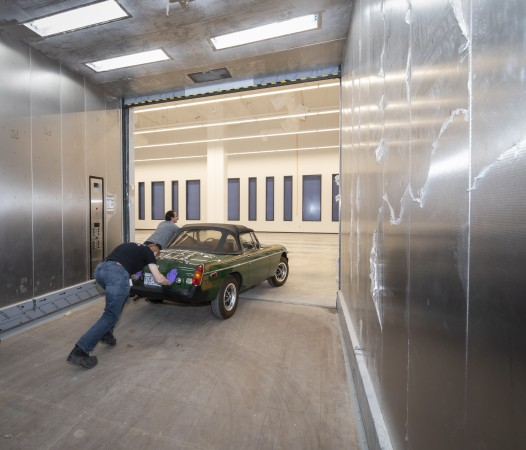 A green sports car is pushed off of the large freight elevator.