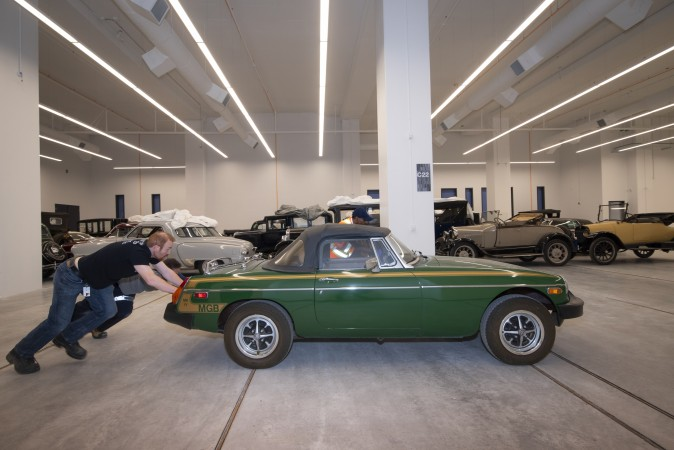 Two men push a green sports car next to a large collection of vehicles.