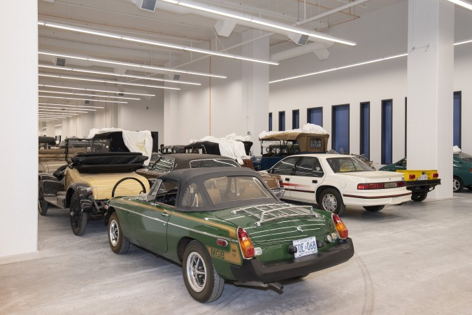A rear view of a green sports car, lined up with dozens of other vehicles in a large storage space.