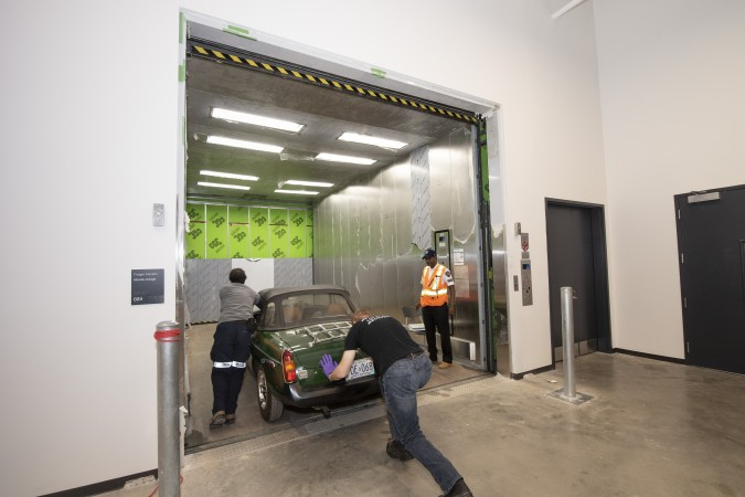 Two men push a green sports car into the oversized freight elevator.