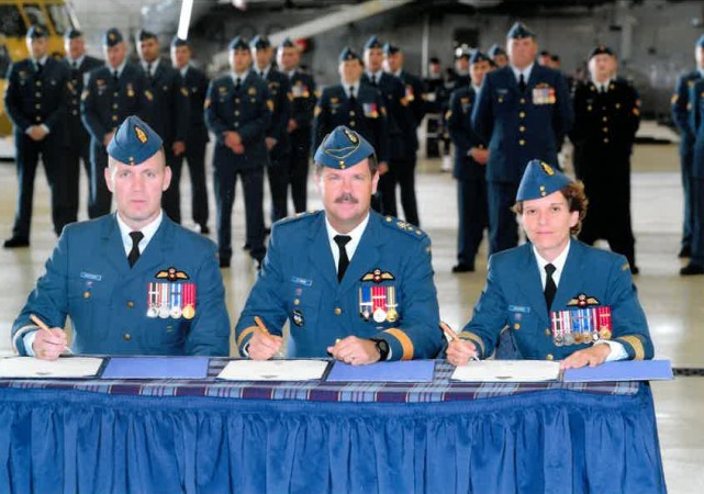 Three people in blue military uniforms sign documents at a table, while uniformed men stand behind them.