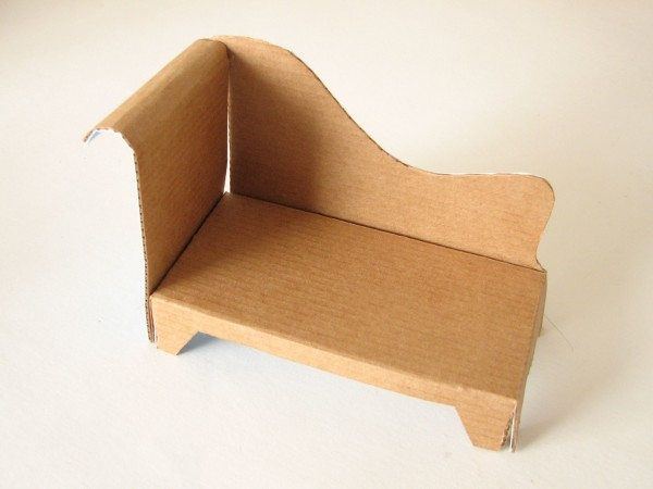 A miniature couch made out of cardboard
