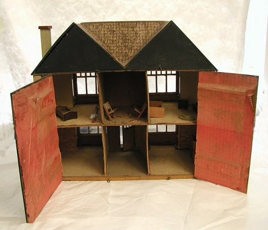 A six-room cardboard dollhouse on a wooden base that opens at the back