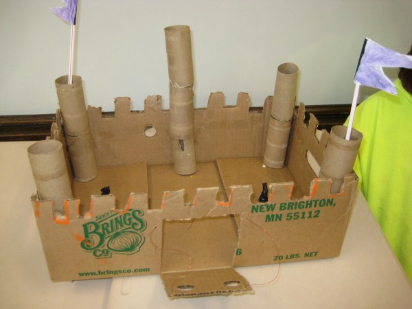 A toy castle constructed out of cardboard, toilet paper rolls, and straws