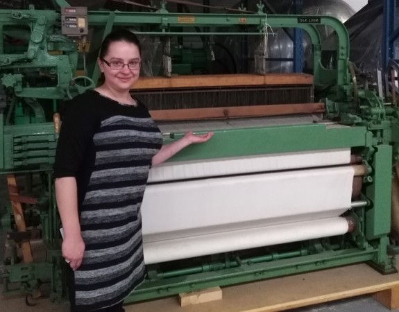 A large, green industrial loom that has a number of cranks and wheels.