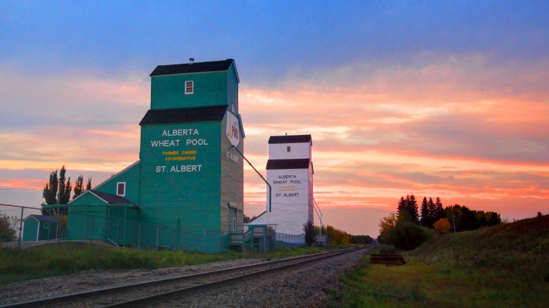 Two tall grain elevators stand alongside a railway track, with a beautiful sunset in the background.