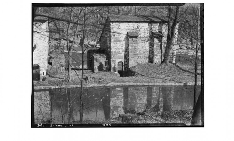 A black-and-white photograph shows stone brick buildings on a riverbank.