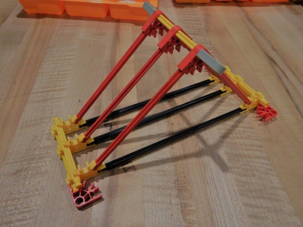A completed catapult base made out of K'NEX. A square base with a pyramid built above it.
