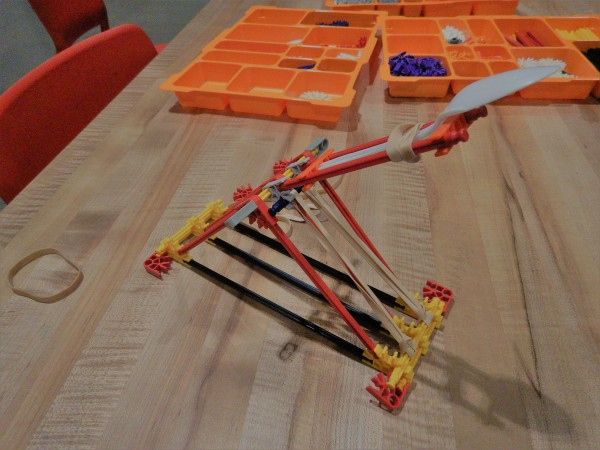 A completed catapult made out of K'NEX and a plastic spoon