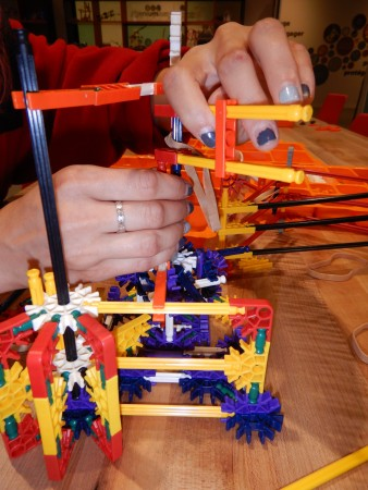 A museum guide in the process of building a super robust and complicated K'NEX catapult