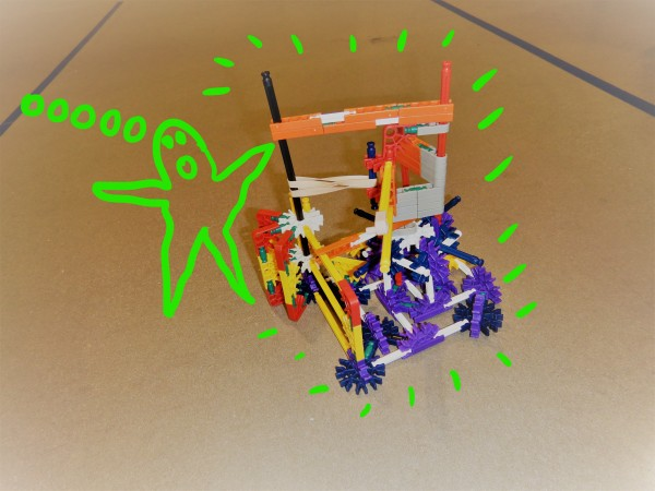 A completed sideways K'NEX catapult that launches a projectile from the side, instead of over the top. The image has a cartoon drawing of a green monster standing next to the catapult.