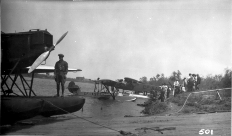 Image is a black-and-white photograph showing three sea planes at a shore where people are standing. In the foreground, one man is standing on one of the floats of the closest plane.