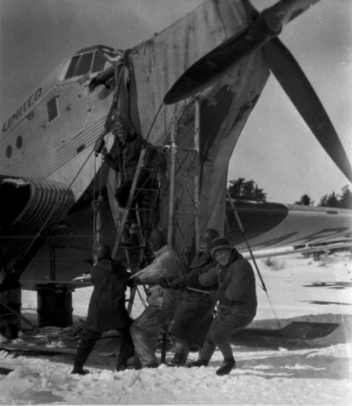 Image is a black-and-white photograph showing four men pulling on a rope attached to a pulley, with another man standing on a ladder. They are next to the nose of a large aircraft.