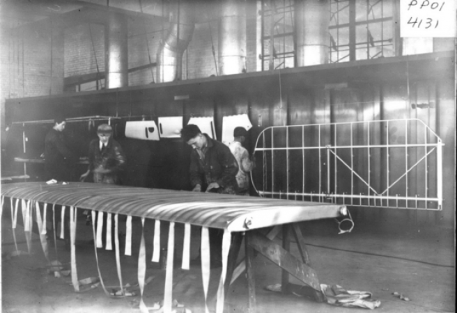 Image is a black-and-white photograph showing a shop floor, where men are building aircraft wings. Two men stand behind the frame of a wing propped up horizontally with strips of fabric visibly hanging from it.