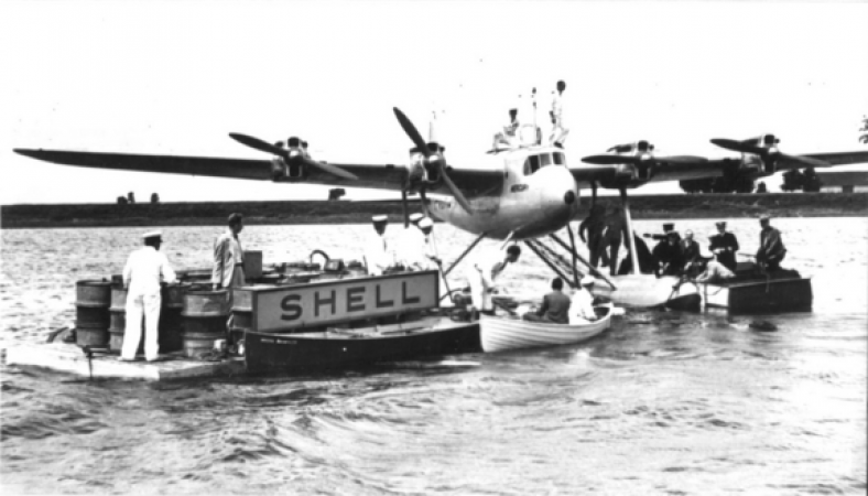 Black and white photograph showing a seaplane being refueled on the water at a dock with a Shell sign on it.