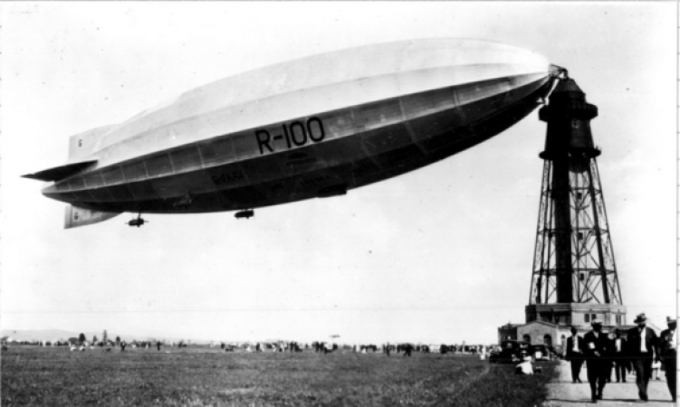 Black and white photograph of the R-100 airship docked at a mooring station tower that rises up above the people walking in the foreground.