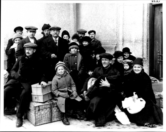 Image is a black-and-white photograph of a group of immigrants standing or sitting with luggage, perhaps on a station platform. They are dressed warmly with hats and scarves.