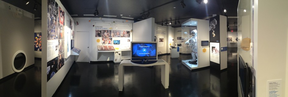 A wide-angle view of a large space inside a museum, with white walls and a black floor. Colourful panels are visible, as well as a computer screen and a spacesuit inside a glass case.