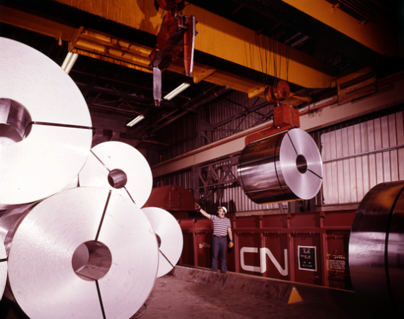 Image is a colour photograph showing a worker pointing up at coils of aluminum that is being unloaded in a CN yard.