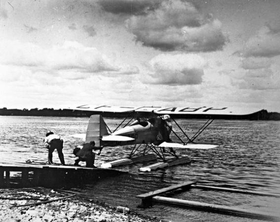 Image is a black-and-white photograph showing a seaplane at the end of a dock. Two men are on the deck and are holding on to the aircraft with a rope.