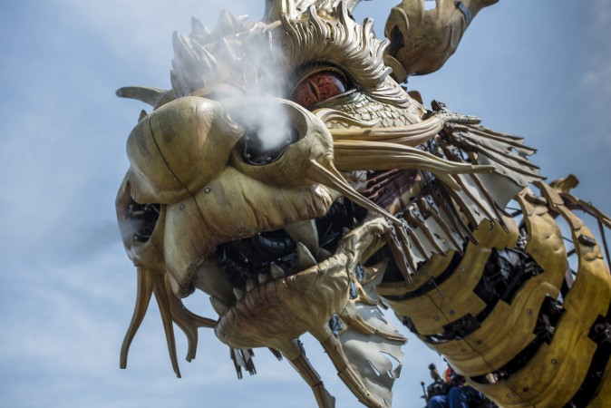 A building-sized mechanical dragon with steam coming from its nostrils.