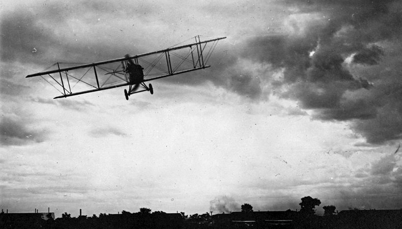 A black-and-white image depicts a front view of a biplane flying over flat land.