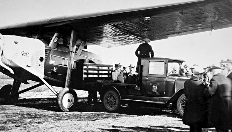 A black-and-white image shows a dozen men standing around a truck and an airplane.