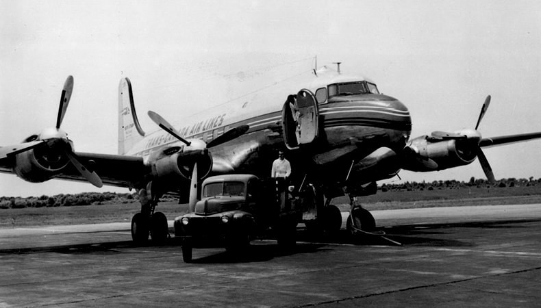 A black-and-white image shows a large aircraft with its door open, along with a truck with a man.