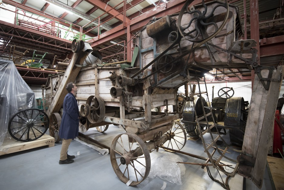A curator examines a piece of historical farm equipment in a warehouse.