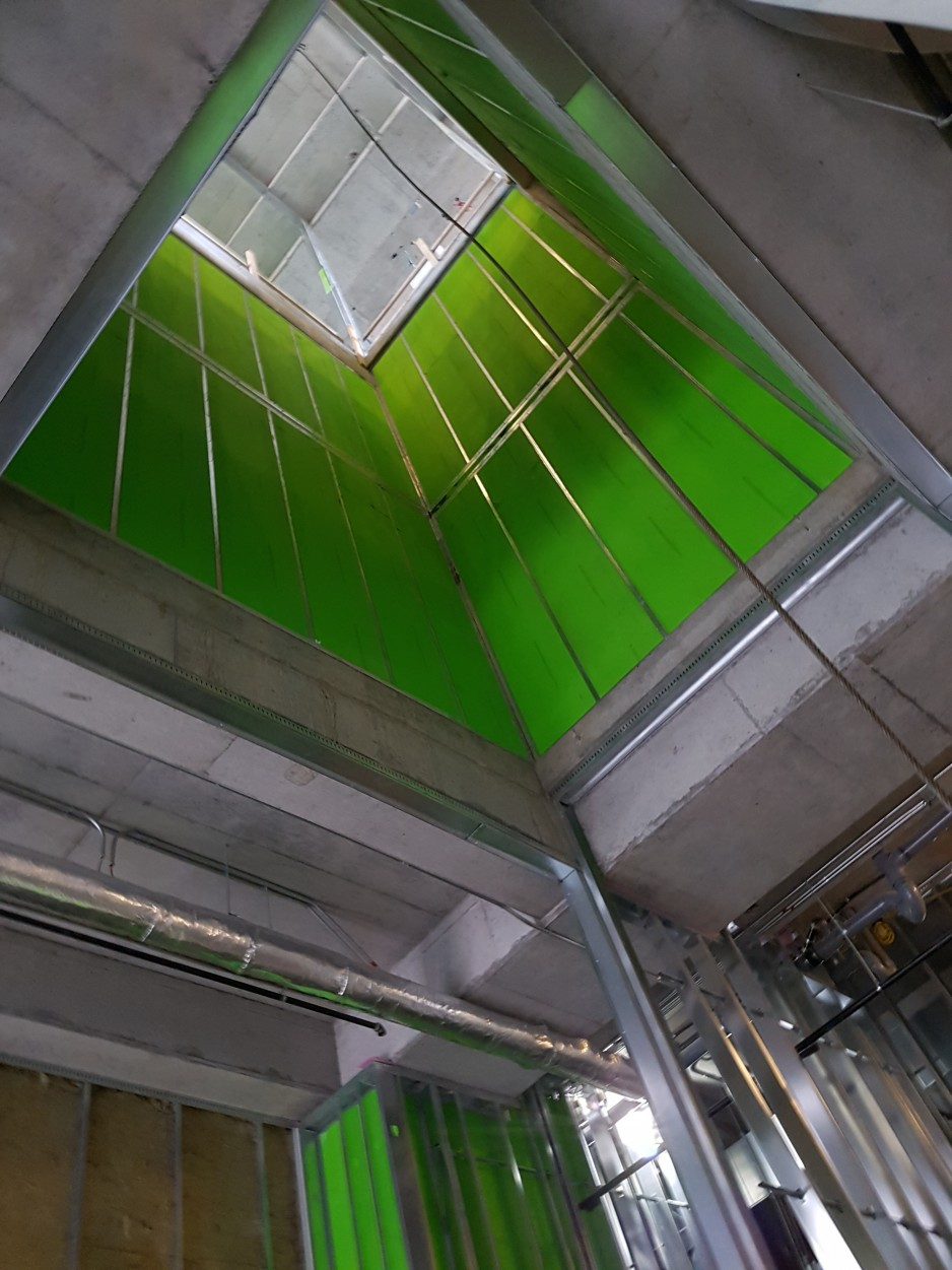 Looking upward into the shaft of a modern, green-tinted elevator shaft.