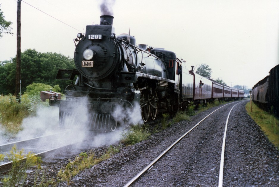 Steam billows around a train as it rolls along the railway tracks.