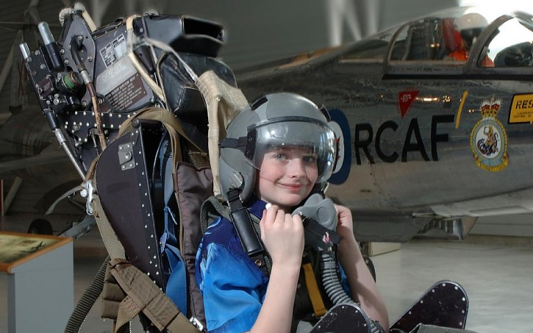 A smiling child sits in an airplane seat wearing a helmet.