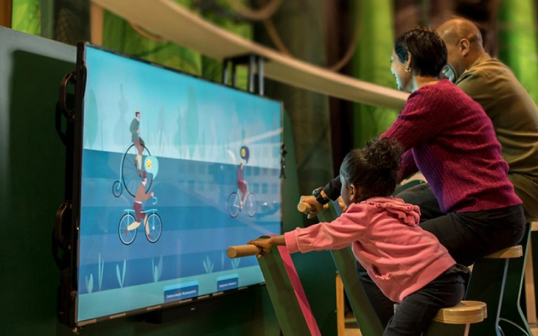 A child and two adults pedal stationary bicycles in front of a screen in an exhibition.