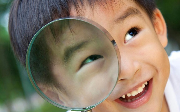 Child looking through a magnifying glass.