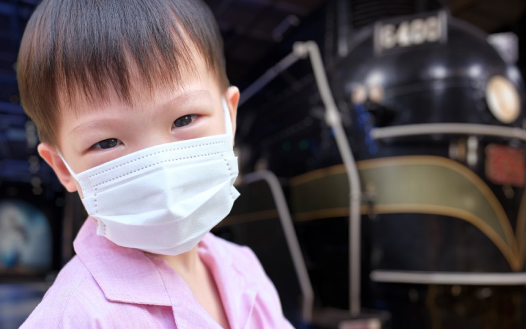 young boy wearing a mask, in the background you can see a locomotive in soft focus.
